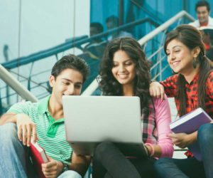 Students sitting on steps using laptop